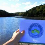 """Le Léguer, fleuve des Côtes d'Armor en Bretagne, est labellisé """"Sites Rivières Sauvages"""" depuis le 20 octobre 2017. Le logo bleu du label devant le fleuve Léguer, sous le ciel bleu."""