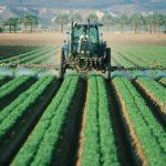 Un tracteur agricole répandant des pesticides dans un champ
